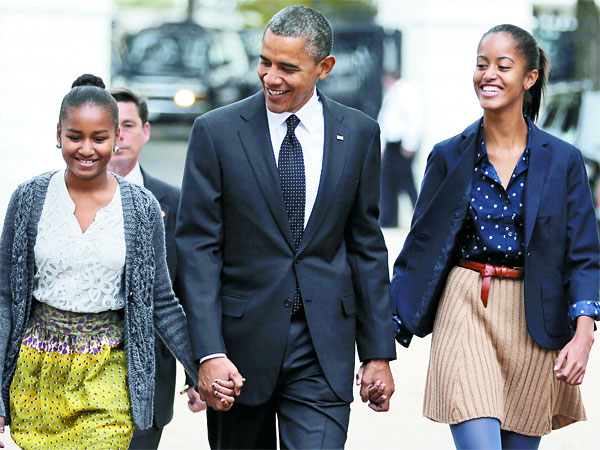 President Obama walking with his daughters